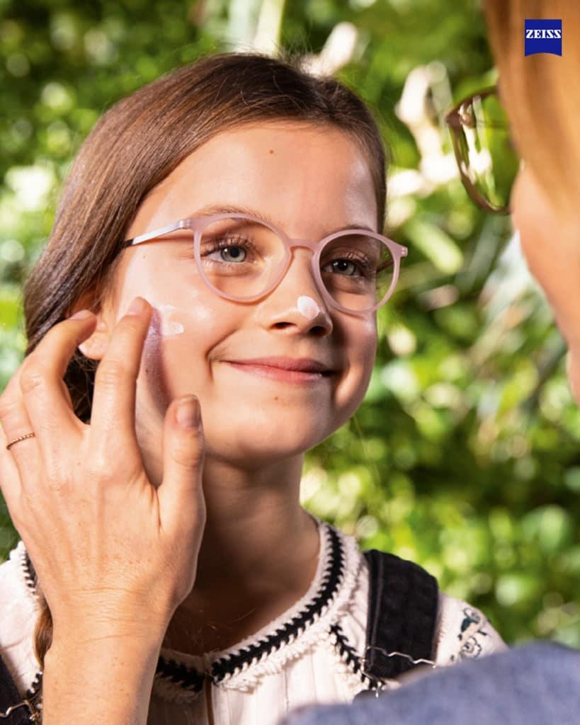 Pige med briller får smurt solcreme på kunderne